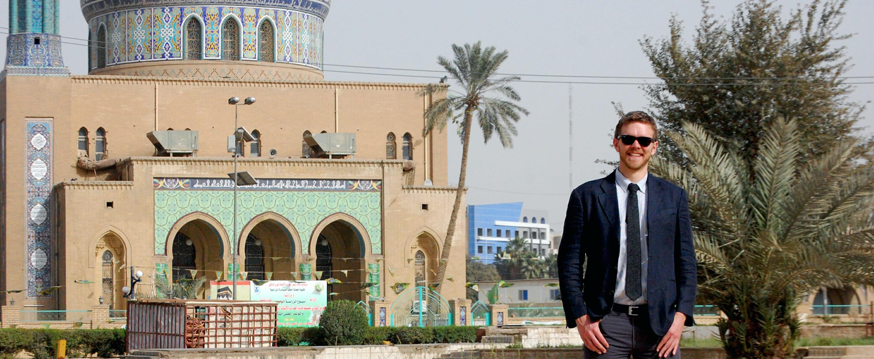 Ben Van Heuvelen in Baghdad, standing next to a mosque.
